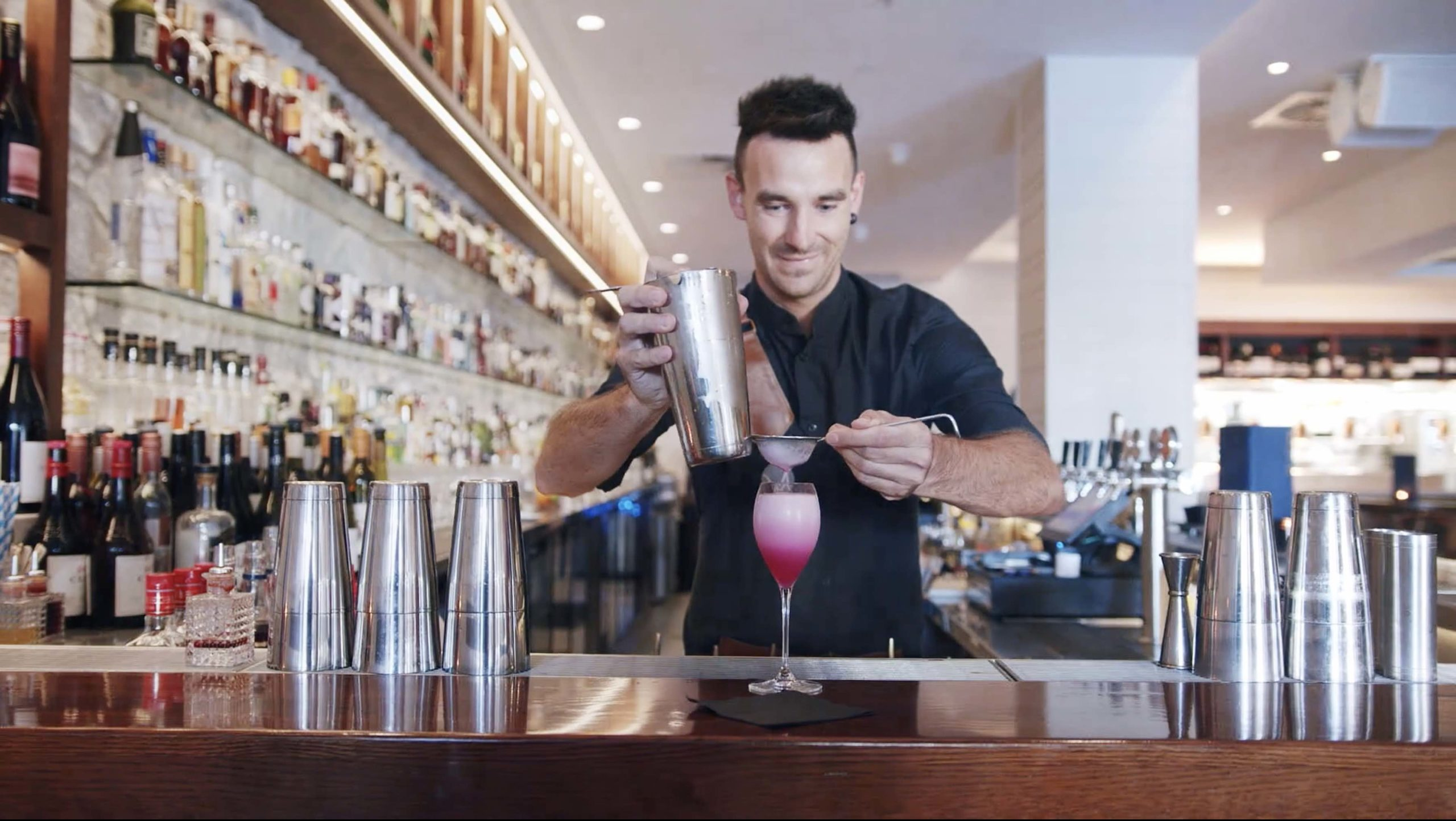 man making a pink cocktail in Miss Moneypenny Broad beach