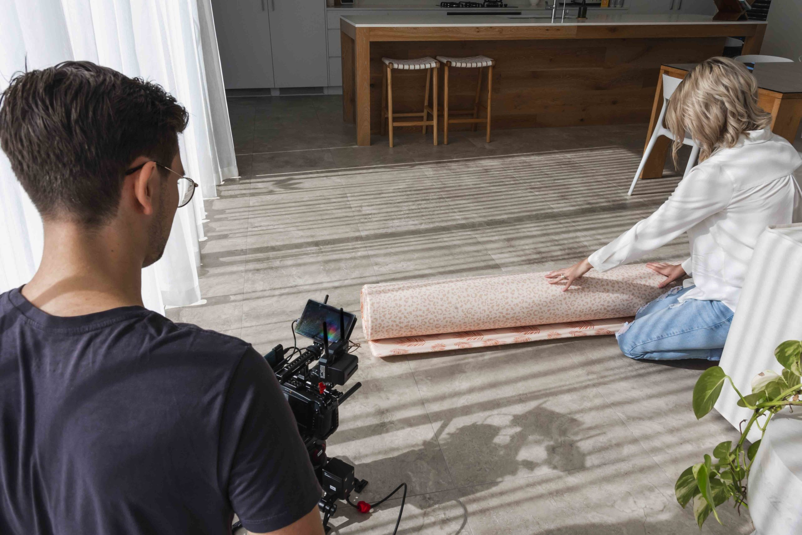 Woman rolling out a mat while Benjamin is filming with a slider
