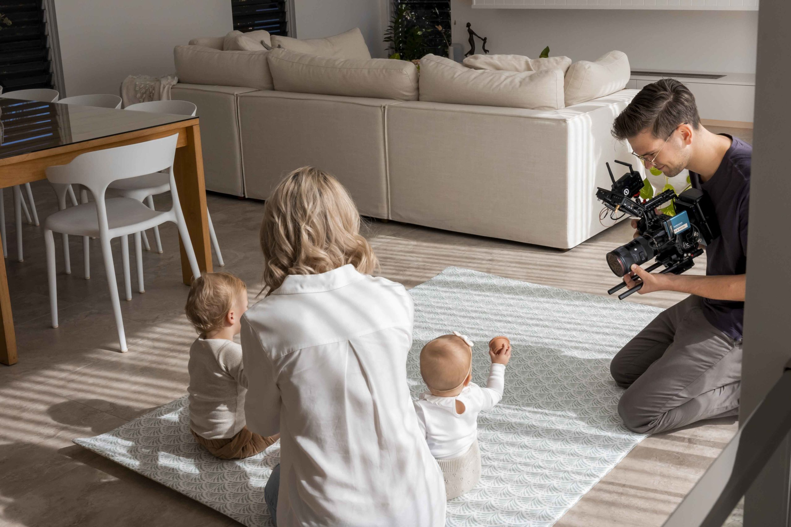 Family playing on a Luxe at Plays mat while Benjamin is filming