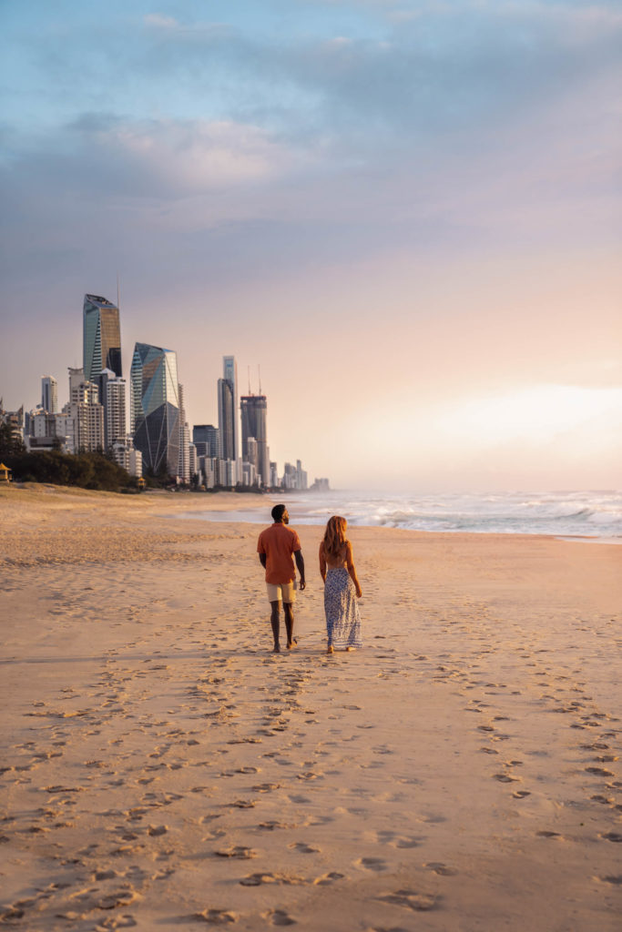 Couple walking on beach at Gold coast for Tourism Queensland